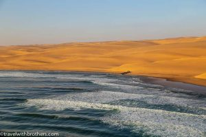 Namibia, Namib desert scenic flight - a shipwreck surrounded by high dunes and ocean