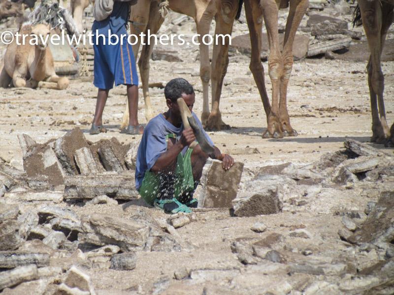 Dancalia, un lavoratore intento a modellare la lastra di sale